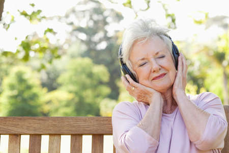 70s adult: Woman listening to music using headphones with her eyes closed and her head tilted LANG_EVOIMAGES