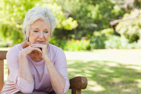 70s adult: Woman with a disheartened expression sitting on a wooden bench in a park