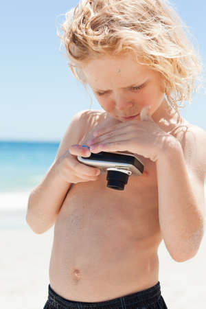niños rubios: El niño pequeño en la playa echar un vistazo a la pantalla de una cámara digital