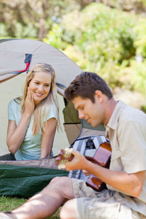 serenade: A man plays a serenade for his girlfriend as he sits beside the tent she is in