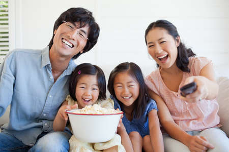tv show: Family smiling and laughing as they watch a tv show while sitting on the couch