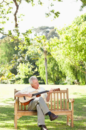 player bench: Man with his eyes closed playing a guitar while sitting on a bench in a park