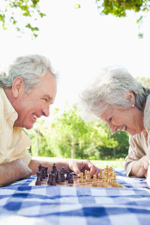 70s adult: Man and a woman smiling while looking at a chess board in the park