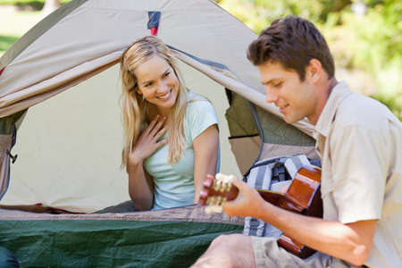 impress: A man playing the guitar to impress his girlfriend as they camp together