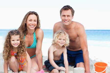 sandcastle: Cheerful family building a sandcastle on the beach