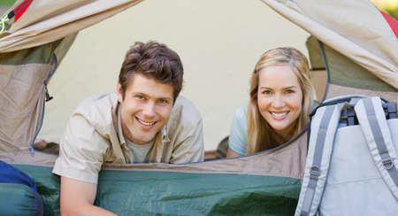 middleaged: A camping couple smile from inside the tent together