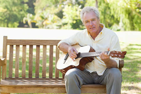 player bench: Man looking ahead of him as he plays a song on a guitar as he sits on a bench in the park
