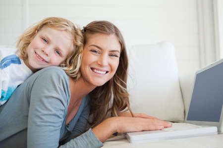 lie forward: A smiling mother and son lie on the couch and uses the laptop as they look forward LANG_EVOIMAGES