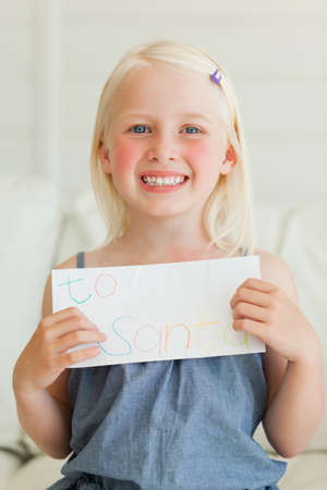addressed: A happy child smiling as she has written her letter to send to Santa