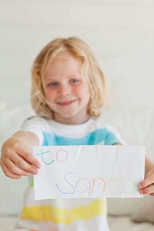 addressed: A small smiling boy holds his letter to santa in front of him