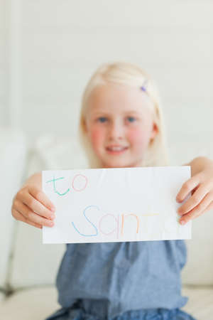 addressed: A letter addressed to Santa is in the focus with the smiling girl in the background LANG_EVOIMAGES