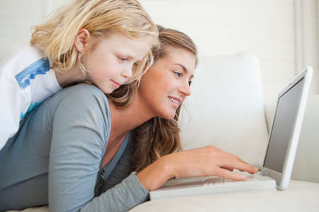 interacts: A smiling woman lies on the couch and interacts with her laptop as her daughter lies on top of her