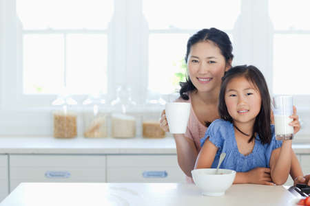 breakfast room: A daughter with her mother at the table as the girl gets ready to eat cereal