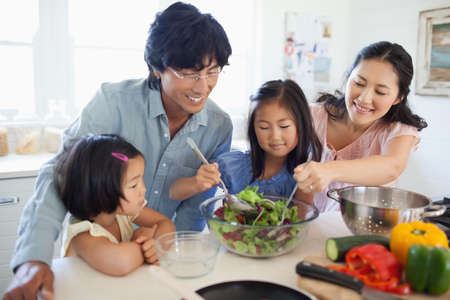 to toss: A family all help and watch to make and toss a salad together in the kitchen