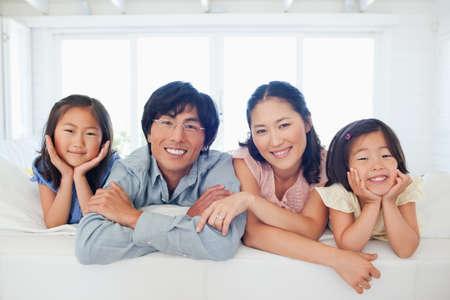 to kneel: La familia sonriendo mientras se arrodillan juntos en el sof� LANG_EVOIMAGES