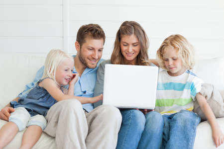 television show: The smiling family sit on the couch together as they watch a television show on the laptop