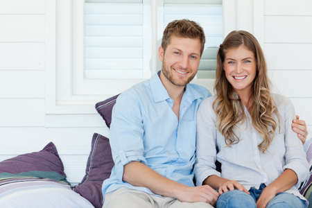 sit around: A smiling loving couple sit outside together as the man has his arm around her