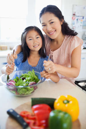 to toss: A smiling mother and daughter look ahead as they toss a salad together