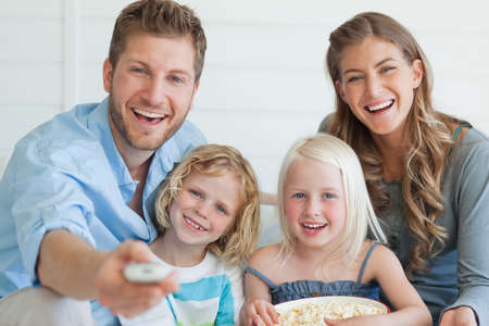 ver tv: Una risa reloj tv familia que el padre cambia el canal y la hija sostiene un cuenco de palomitas de maíz LANG_EVOIMAGES
