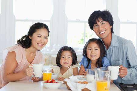 A family sits to enjoy breakfast together at the table