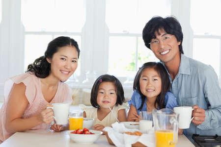 Eine Familie sitzt Frühstück zusammen am Tisch zu genießen