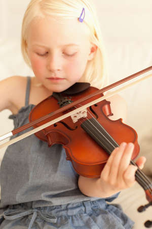 sweetly: A small girl plays the violin sweetly LANG_EVOIMAGES