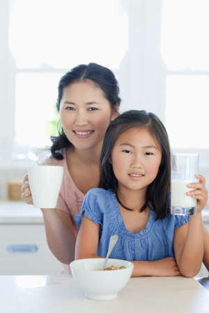 A girl and her mom smiling and at the table as the girl is about to eat cereal