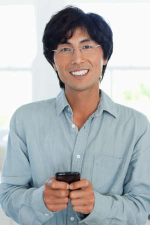 one mid adult male: A close up shot of a man smiling as he uses his phone to send a text LANG_EVOIMAGES