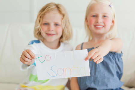 addressed: A letter addressed to Santa being held by a brother and sister. LANG_EVOIMAGES