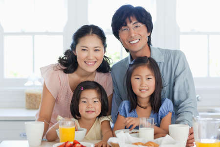 partake: A smiling family look forward as they are about to partake in some lovely food
