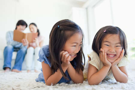 laying forward: The smiling girls are lying on the carpet while the parents read a book together