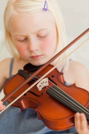 sweetly: A girl with closed eyes plays the violin sweetly