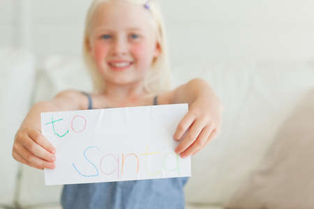 addressed: A smiling girl holding her letter to Santa in front of her.