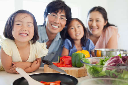 unprepared: A salad on the table unprepared which will be made by the smiling family in front of it