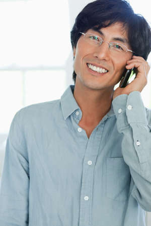 one mid adult male: A close up of a man on the phone smiling while looking forward LANG_EVOIMAGES