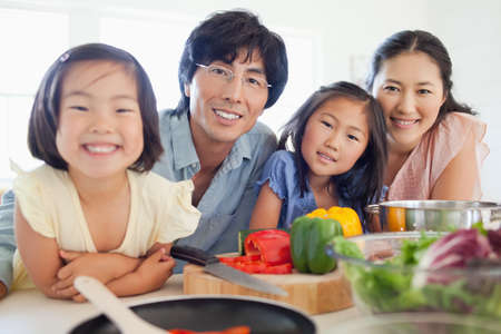 get ready: A close up shot of a family smiling as they get ready to prepare a salad LANG_EVOIMAGES