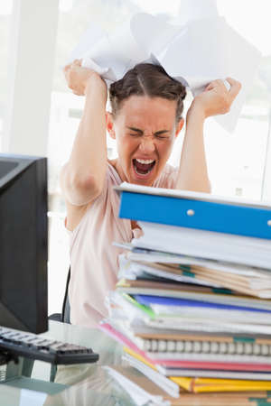 too much work: Businesswoman with too much work goes crazy in a bright office
