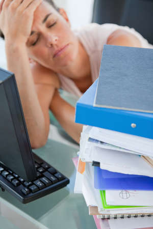 too much work: Tired businesswoman getting too much work in a bright office