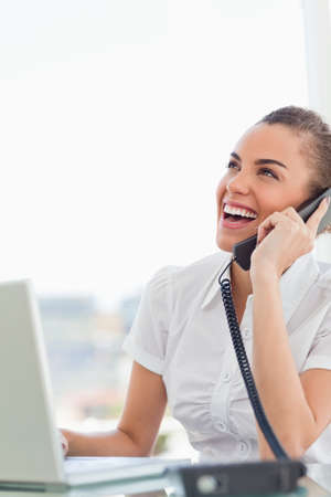 frizzy: Frizzy haired woman laughing while calling in a bright office LANG_EVOIMAGES