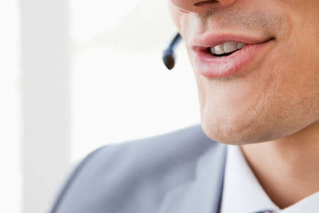 mouth smile: Close-up of a mans mouth speaking with a headset in a bright office