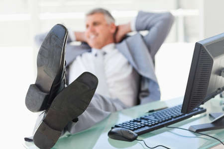 feet on desk: Boss with feet on his desk  in a bright office