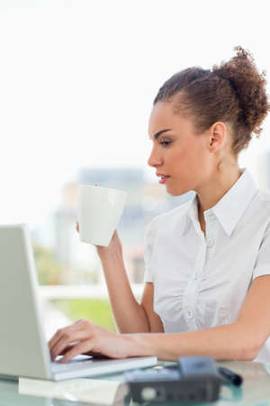 frizzy: Frizzy woman tapping on her laptop while drinking a coffee in a bright office LANG_EVOIMAGES