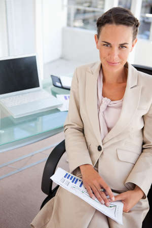 businesswoman suit: Businesswoman in a beige suit with diagrams smiling in a bright office