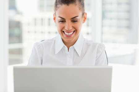 frizzy: Frizzy haired smiling woman working with a laptop in a bright office