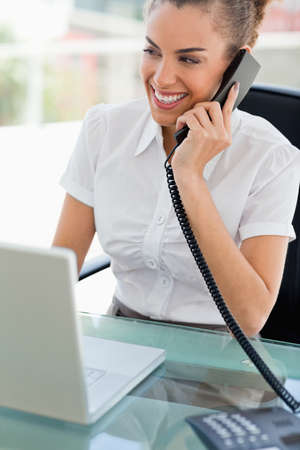 phoning: Frizzy haired woman smiling while phoning in a bright office LANG_EVOIMAGES