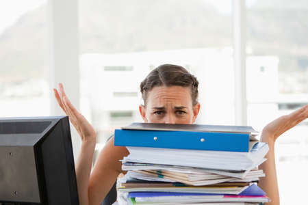 too much work: Businesswoman getting too much work in a bright office