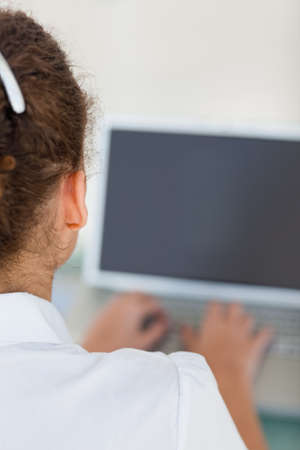 tanned woman: Tanned woman using a laptop with black screen in a bright office