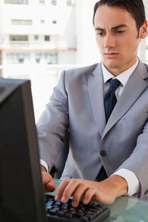 businessman working at his computer: Businessman working on his computer in a bright office