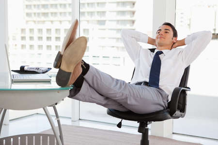 feet on desk: Happy businessman feet on his desk in a bright office LANG_EVOIMAGES
