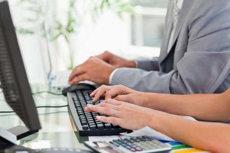 persona escribiendo: Las personas que trabajan juntos en los ordenadores en una oficina brillante